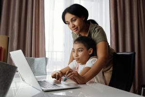 a mother and a child doing online schooling
